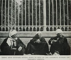 Three Arab Effendis Sitting Down to Rest on the Pavement Outside the Esbekiya Gardens. (1911) - TIMEA.jpg