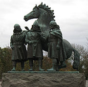 Photograph of a copper statue (coated with green patina) of three men casually discussing with a horse in the background.