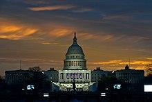 US Capitol bij zonsopgang, grotendeels verduisterd maar met de koepel van buitenaf verlicht