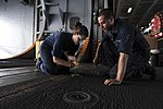 U.S. Navy Boatswain's Mate Seamans Chelsea Smith, left, and Gregory Muir perform maintenance in the hangar bay aboard the aircraft carrier USS Nimitz (CVN 68) in the Indian Ocean June 7, 2013 130607-N-TX484-067.jpg