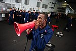 U.S. Navy Damage Controlman 1st Class Damarcus McCoy announces upcoming events during a damage control olympics competition June 10, 2013, aboard the aircraft carrier USS George H.W. Bush (CVN 77) in 130610-N-XE109-133.jpg