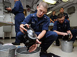 U.S. Navy Machinist's Mate 3rd Class Donny I. Johnson, foreground, washes a gas mask after a chemical, biological and radiological (CBR) warfare drill aboard the aircraft carrier USS George H.W. Bush (CVN 77) in 110730-N-JD217-018.jpg