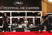 "The Edge, Adam Clayton, and Larry Mullen, Jr. performing outside a building on red carpet, with a sign in the background reading ""Festival de Cannes""."