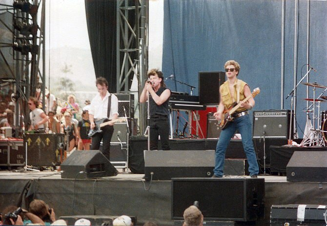 U2 playing on an outdoor stage. The Edge is on the left playing guitar, Bono in the center with a microphone, and Adam Clayton on the right playing bass guitar. A drum set is partially visible on the right side.