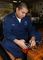 US Navy 040227-N-0009S-001 Aviation Support Equipment Technician 1st Class Paul A. Lazo, of San Diego, repairs wheel chock lanyards.jpg