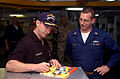 US Navy 041207-N-6125G-101 ASCAR driver John Andretti signs an autograph for Chief Damage Control James Reid aboard the Nimitz-class aircraft carrier USS Harry S. Truman (CVN 75).jpg