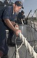 US Navy 060903-N-9851B-001 Seaman Edward Castoire heaves in a mooring line as the Arleigh Burke-class guided missile destroyer USS Hopper (DDG 70) moors in Guam for a port visit.jpg