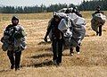 US Navy 070815-N-9860Y-048 Members of Explosive Ordnance Disposal Mobile Unit (EODMU) 11 walk with their parachutes after landing during a jump to honor fallen comrades in Outlying Field.jpg