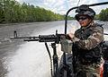 US Navy 090508-N-6403R-157 JOHN C. STENNIS SPACE CENTER, Miss. (May 8, 2009) Brazilian Federal Police agent Henrique Cesar mans an M240B machine gun on a patrol boat.jpg