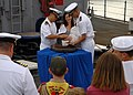 US Navy 090917-N-6692A-047 Lt. John Madea holds his daughter as she is baptized with holy water from the ship's bell of the amphibious dock landing ship USS Tortuga (LSD 46).jpg
