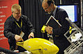 US Navy 101109-N-7676W-172 Michael Rufo, left, with Boston Engineering, explains the BIOSwimmer, a flexible hulled autonomous underwater vehicle.jpg