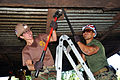 US Navy 111205-A-TF780-080 Steelworker 2nd Class Rejuny Caswell and Marine SSgt. Mario Vargas try to remove a beam from a kitchen roof at Centro Es.jpg