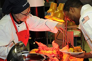 US Navy 111225-N-FU443-038 Culinary Specialist 1st Class Susan Graham serves ham to Culinary Specialist 1st Class Carrol Williams during a Christma.jpg