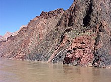 Gray and reddish rock face with rough surface adjacent to a river.