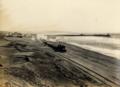 Vista de una locomotora de carga, pasando por la orilla del mar, ca. 1913.png