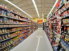 Junk food lines both sides of tall shelves at a grocery store