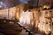 To the right of some stepping stones, a row of lamps illuminates a short artificial waterfall streaming down a honey-colored wall made of limestone bricks.
