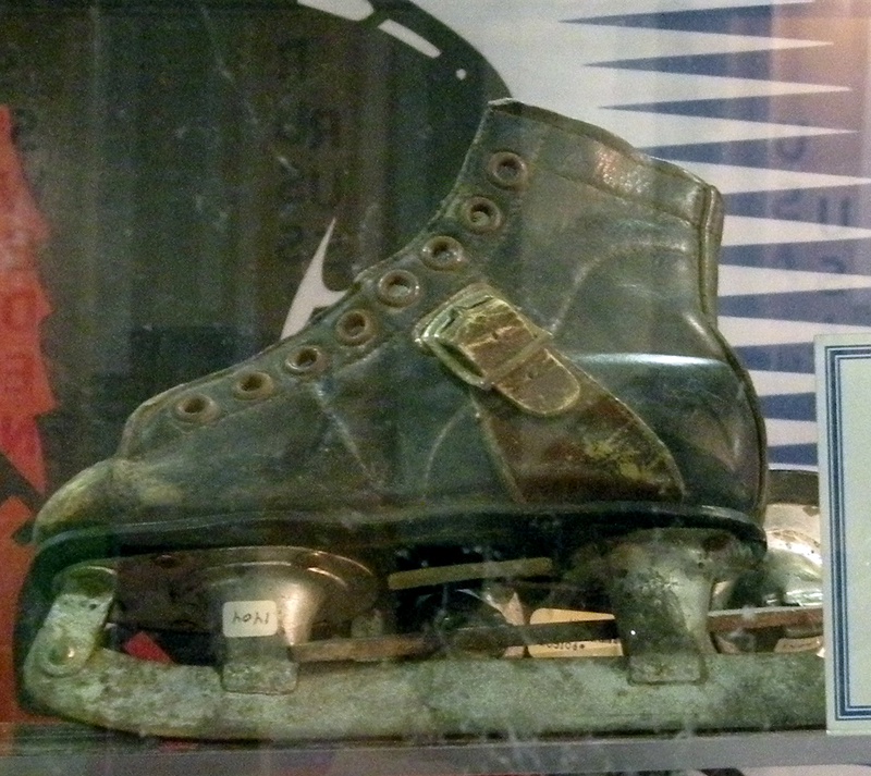 A small pair of ice skates, meant for a small child. The boot is leather and is missing its laces, while the blade is deteriorating and showing significant wear due to age.