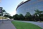 """Die breite, konvexe Fassade einer glasigen Sportarena und der Bürgersteig, der Rasen und die Laternenpfähle davor.  Die Worte """"Xcel Energy Center"""" stehen rot auf dem Stadion."""