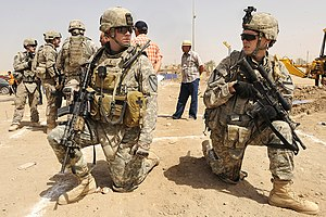 Fraternization - An officer and an enlisted soldier of the US Army converse while they are on patrol in Iraq.