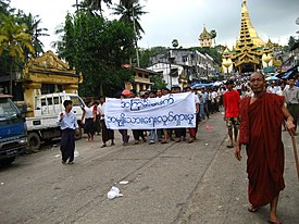 Protesters in Yangon with a banner that reads non-violence: national movement in Burmese, in the background is Shwedagon Pagoda