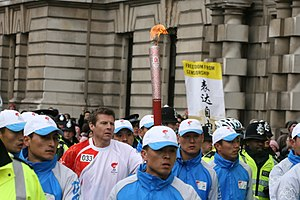 Steve Cram - Cram carries the Olympic Torch for the 2008 Summer Olympics down Whitehall in London surrounded by Police and Olympic officials on 6 April 2008