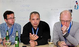Τρεις σύνεδροι, στη μέση ο Κωνσταντίνος Σταμπουλής σε στιγμή που μιλάει.