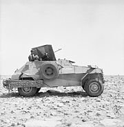 A four-wheeled armoured car, faces to the right, on a stony-desert backdrop.