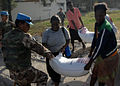 A United Nations peacekeeper from Jordan assists a Haitian woman carrying a 100-pound bag of rice outside Port-au-Prince, Haiti 100213-N-HX866-003.jpg