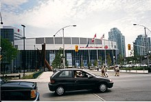 The intersection of a roadway, with a large multi-sport arena in the background