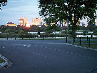 Albert Park and Lake - Aughtie Drive (part of the Grand Prix track) looking east over Gunn Island toward 470 St Kilda Road, St Kilda (main reflection), in the St Kilda Road residential and office precinct