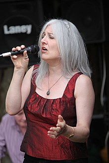 Silver-haired woman wearing a crimson sleeveless top and holding a microphone