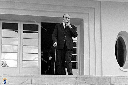 Hoveyda pulling out the pip after a cabinet meeting, January 1965 Amir-Abbas Hoveyda in palace.jpg