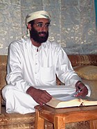 Anwar al-Awlaki sitting on couch, lightened