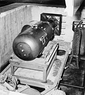 Little Boy unit on trailer cradle in pit on Tinian, before being loaded  into Enola Gay's bomb bay