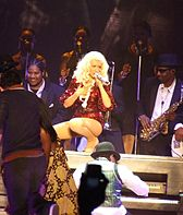 Aguilera wearing a red outfit performing atop a piano