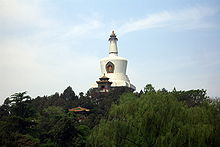 Color photograph of a white, bell-shaped building composed (from bottom to top) of a square base, three round disks of increasingly smaller diameter, a cut reverse cone, and a thinner tapering column with horizontal flutings crowned by the golden statue of a sitting figure. It appears to emerge from a forested area, against the background of a slightly cloudy blue sky.