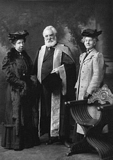 A bearded and elderly man dressed in a formal graduation robe posing with two female university representatives.