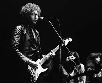 """The Day the World Gets 'Round - Commentators draw comparisons between """"The Day the World Gets 'Round"""" and the work of Bob Dylan, pictured on stage in 1980, during his born-again Christian period."""