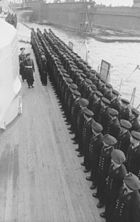 Two men walking by a row of men on the side of ship.
