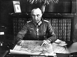 General der Artillerie Paul Bader assis à son bureau, avec une carte. Photo dédicacée manuscrite de l'été 1941