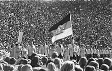 People march behind a large flag surrounded by spectators