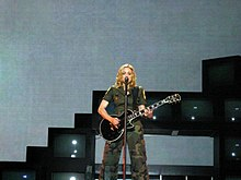Madonna wearing olive green clothes sings to a microphone while holding a black electric guitar in her hands.
