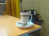 A caffe mocha sitting on a white plate and beige table.
