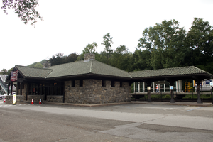 A stone building with a peaked green roof and a porte-cochere on the front. On the left a section of roof extends along some fenced railroad tracks