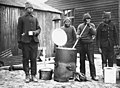 Cooking in a labour camp, Western Front, during World War I. This photograph shows four men cooking and drinking soup from one of the army outside catering boilers. They are all probably members of (4687898545).jpg