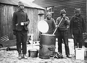 South African Native Labour Corps - Cooking in a labour camp, Western Front, during World War I. This photograph shows four men cooking and drinking soup from one of the army outside catering boilers. They are all probably members of (4687898545)