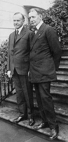 Deux hommes en costume sur les premières marches d'un escalier