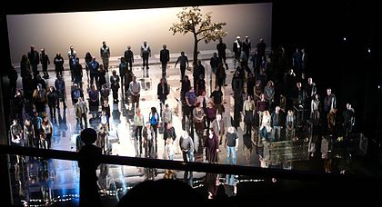 shot from theatre auditorium of performers grouped symmetrically on the stage