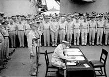 MacArthur is seated a small desk, writing. Two men in uniform stand behind him. A large crowd of men in uniform look on.